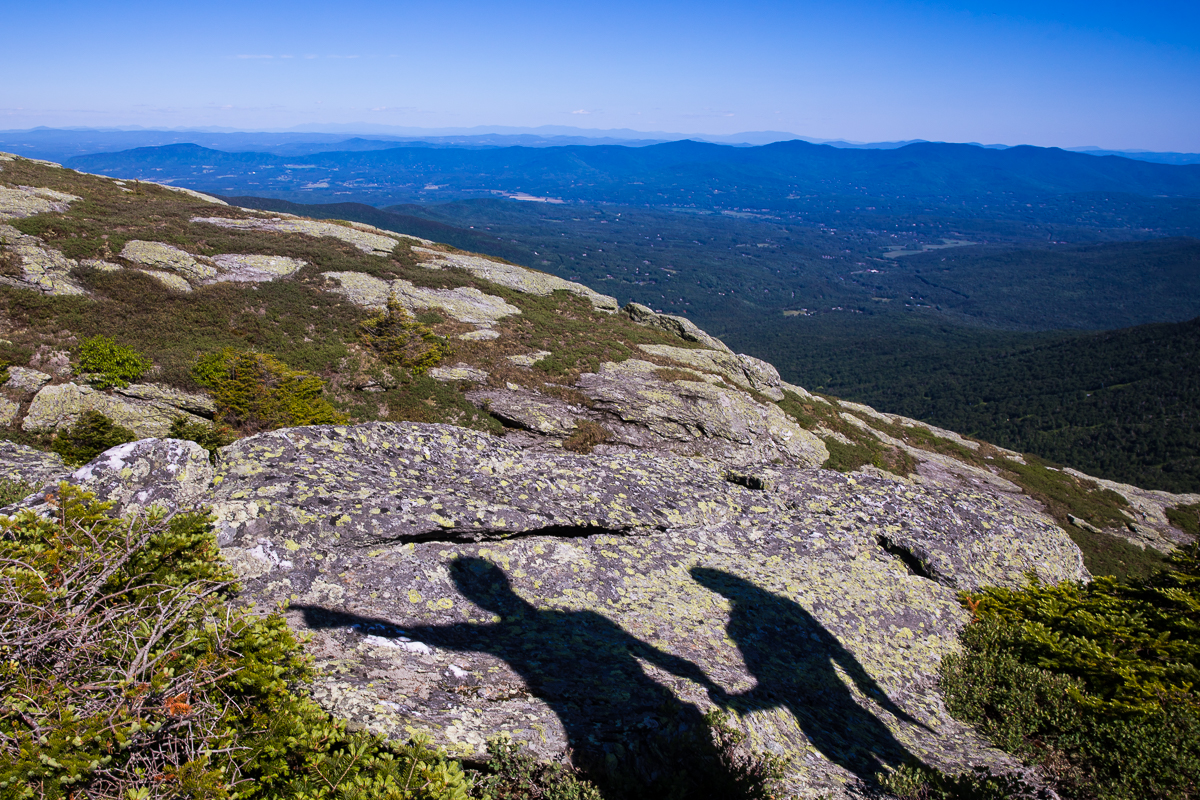 couple holding hands shadow displayed on mountain rocks below with blue mountains in the distance creative angle best artistic photographer central pa