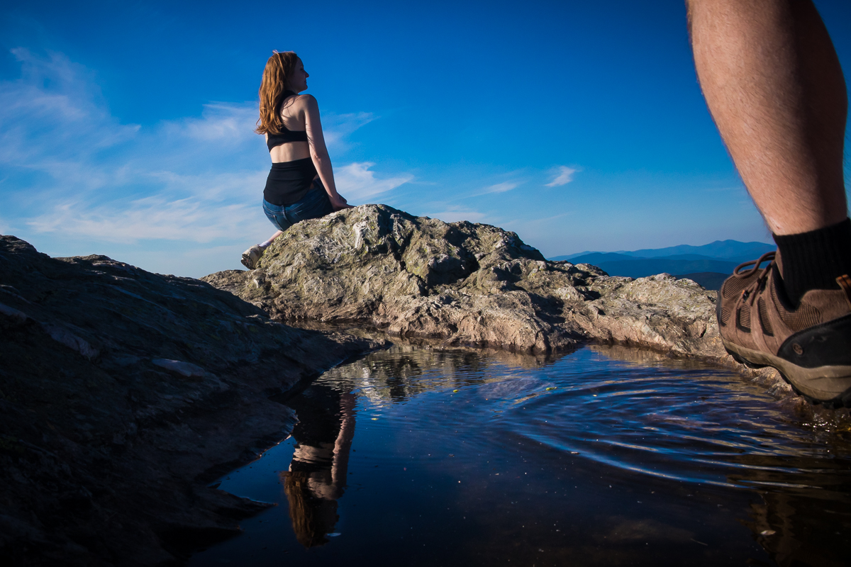girl sitting on rock with reflection in puddle while boy wearing hiking boots walks toward her with blue sky in the background