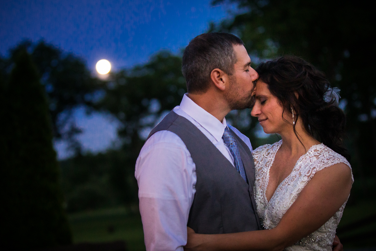 bell mountain estates wedding photographer groom kissing bride on forehead during twilight with sun setting in the background