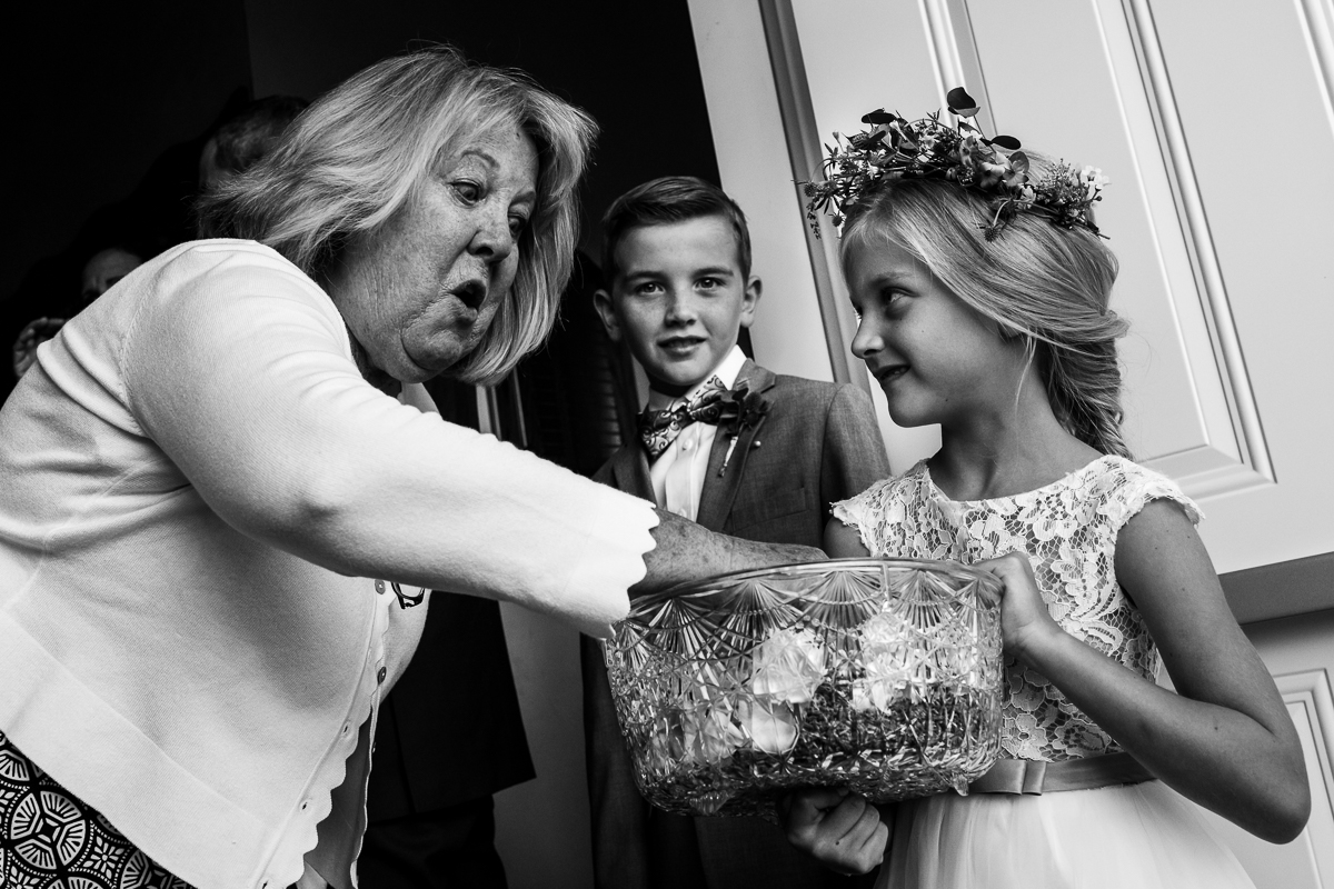 black and white photo of daughter holding flower confetti for ceremony exit while woman reaches in excited