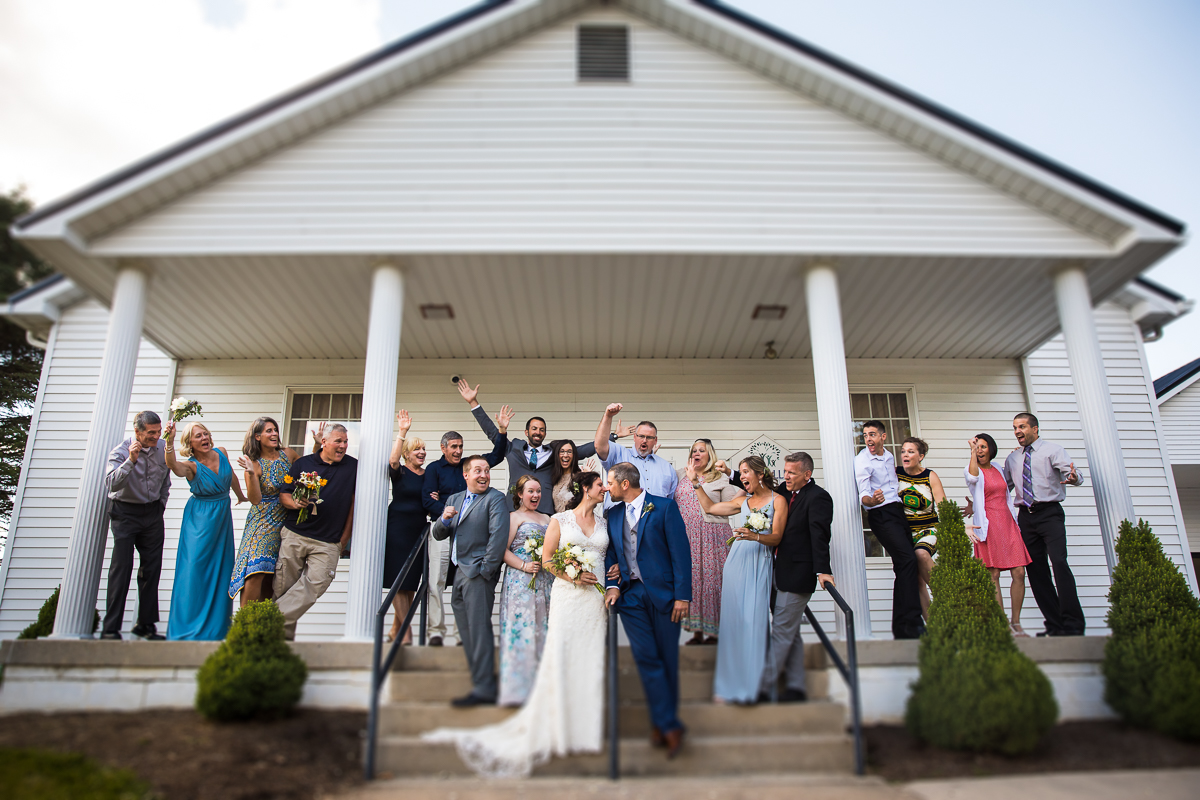 bride and groom standing on steps while friends and family cheer behind them at bell mountain estates wedding ceremony