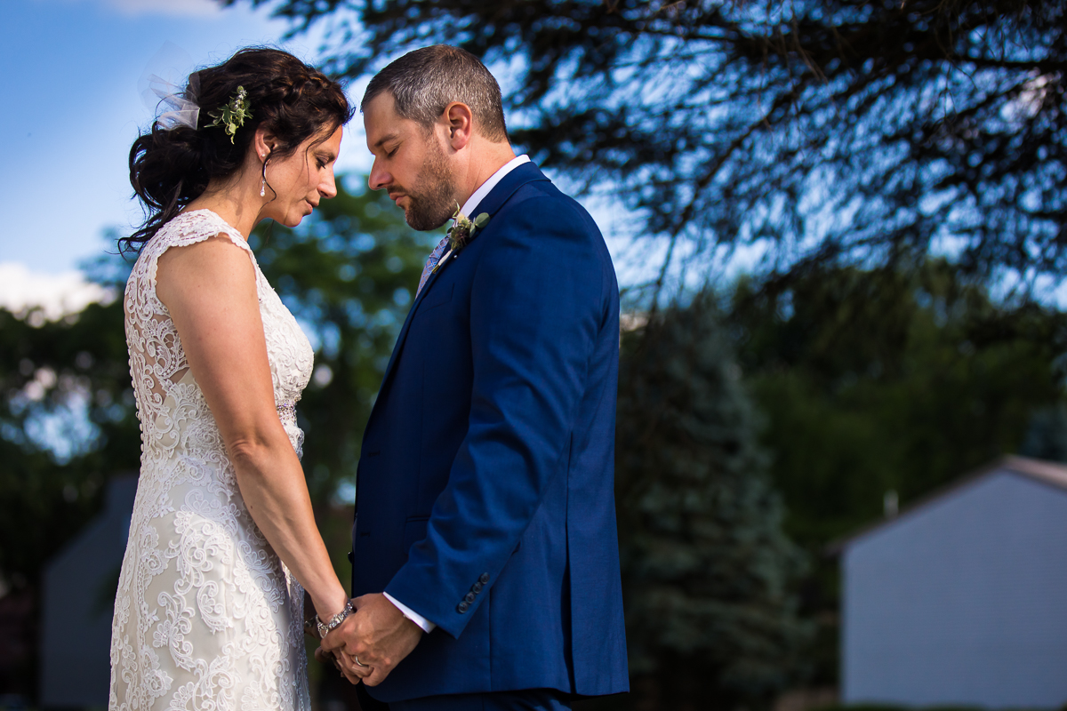 bride and groom standing together holding hands with sunset and trees in background traditional wedding portraits intimate wedding ceremony bell mountain estates wedding