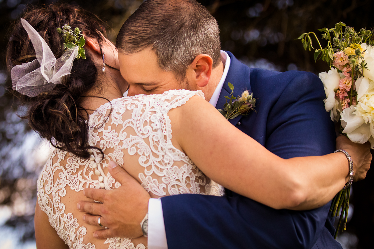bride and groom hugging during portrait time lace detailed dress bride holding bouquet
