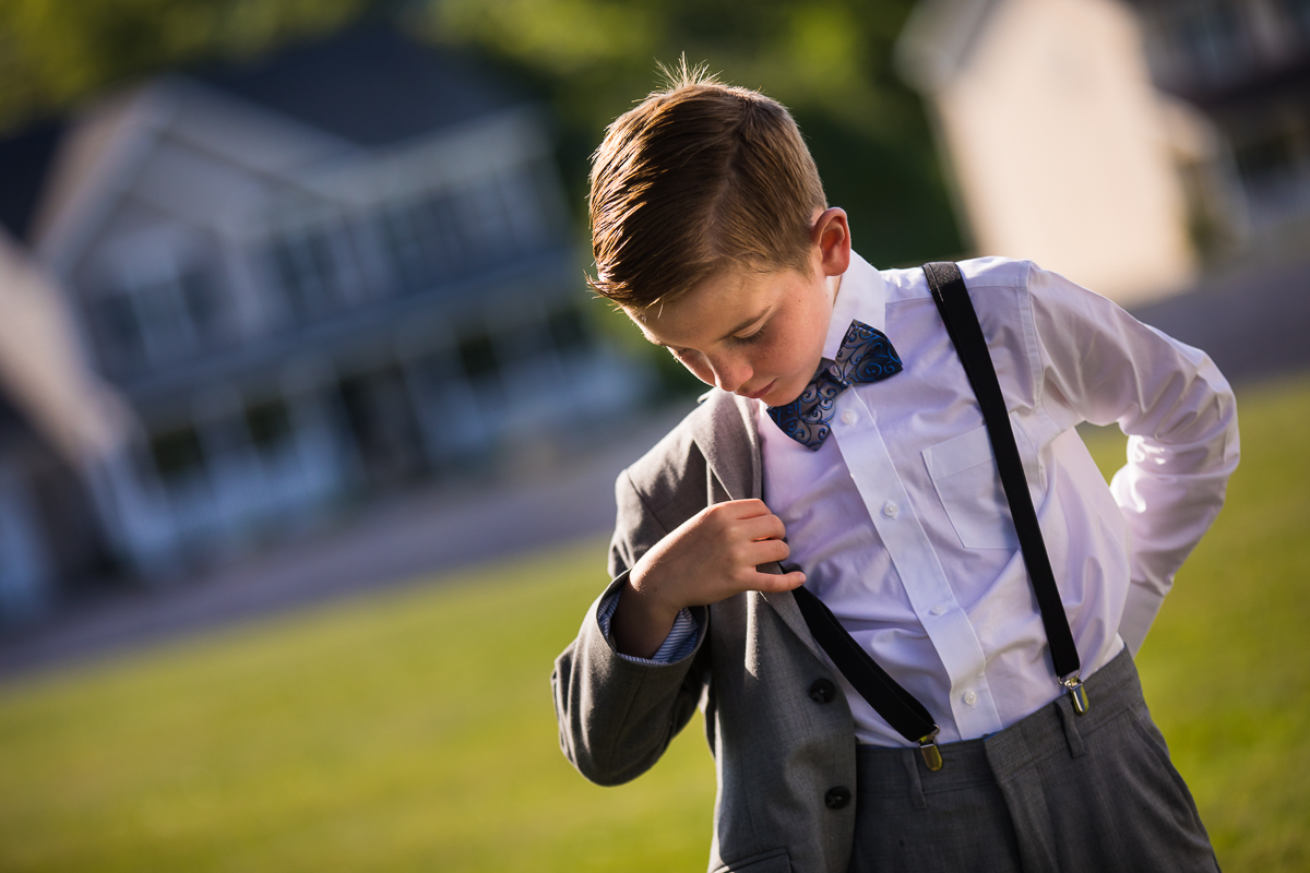 son putting on suit jacket outside wearing white shirt suspenders and blue paisley bowtie