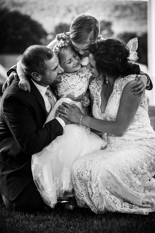black and white photo of bride and groom holding children and smiling at each other during family portraits best central pa wedding photographer