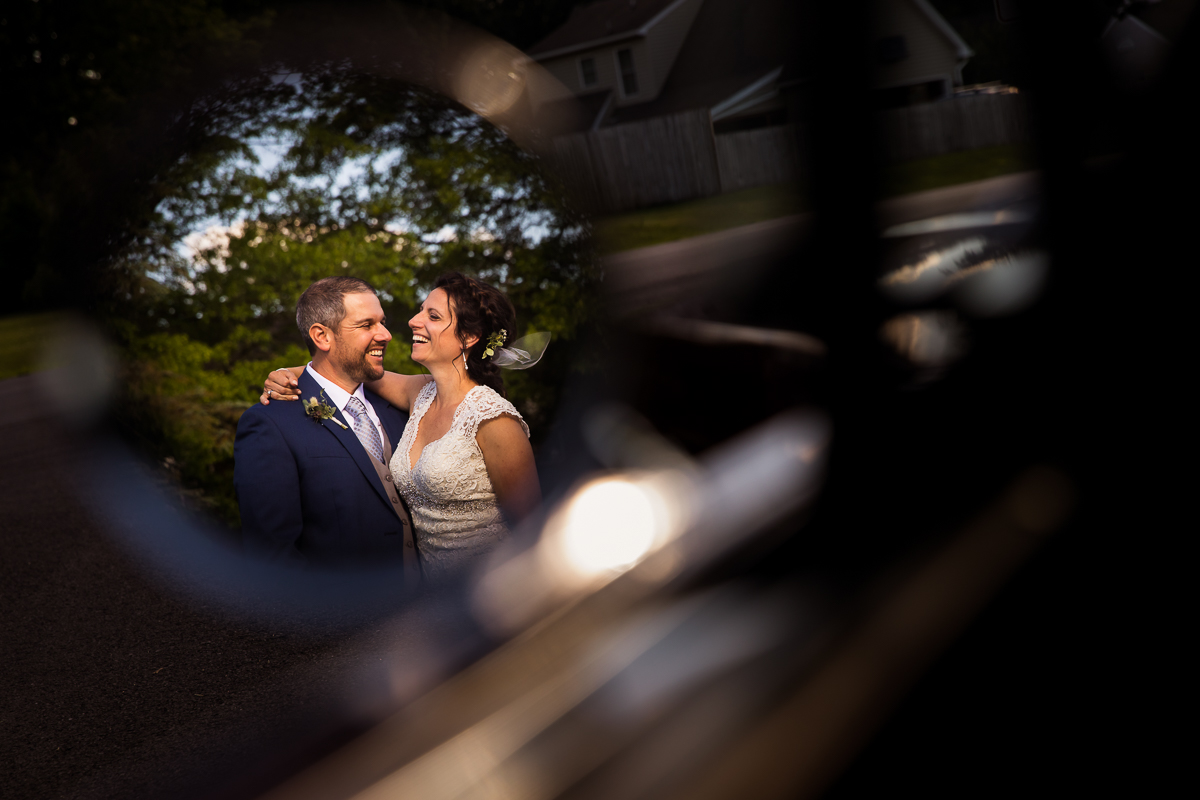 bride and groom smiling at each other from reflection of mustang mirror artistic creative photographer