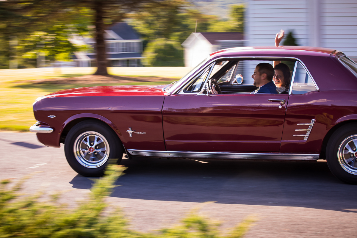bride and groom riding in red Ford Mustang slow motion shutter speed creative artistic photo