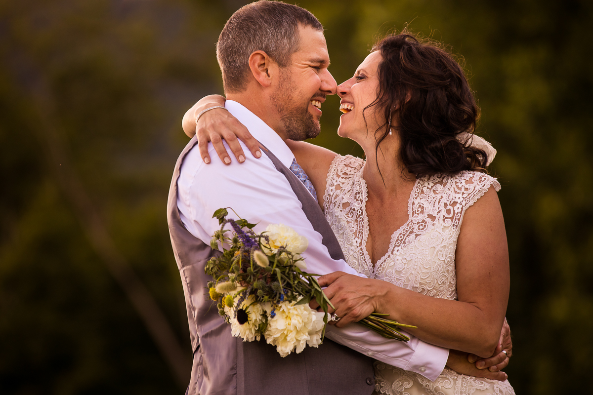bride and groom hugging and smiling and laughing with each other while holding wildflower bouquet best central pa wedding photographer