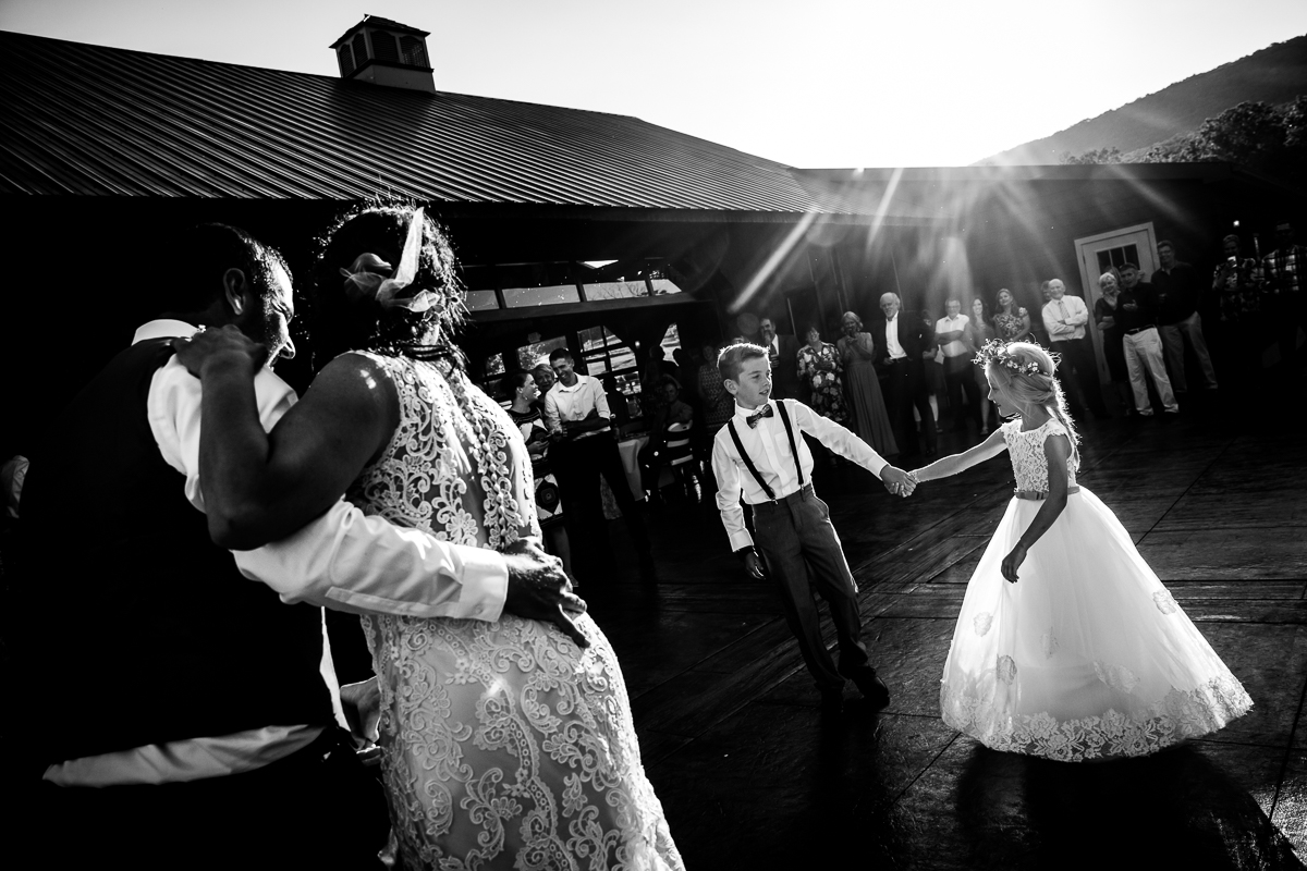 black and white photo of bride and groom dancing while children dance at the same time during first dance