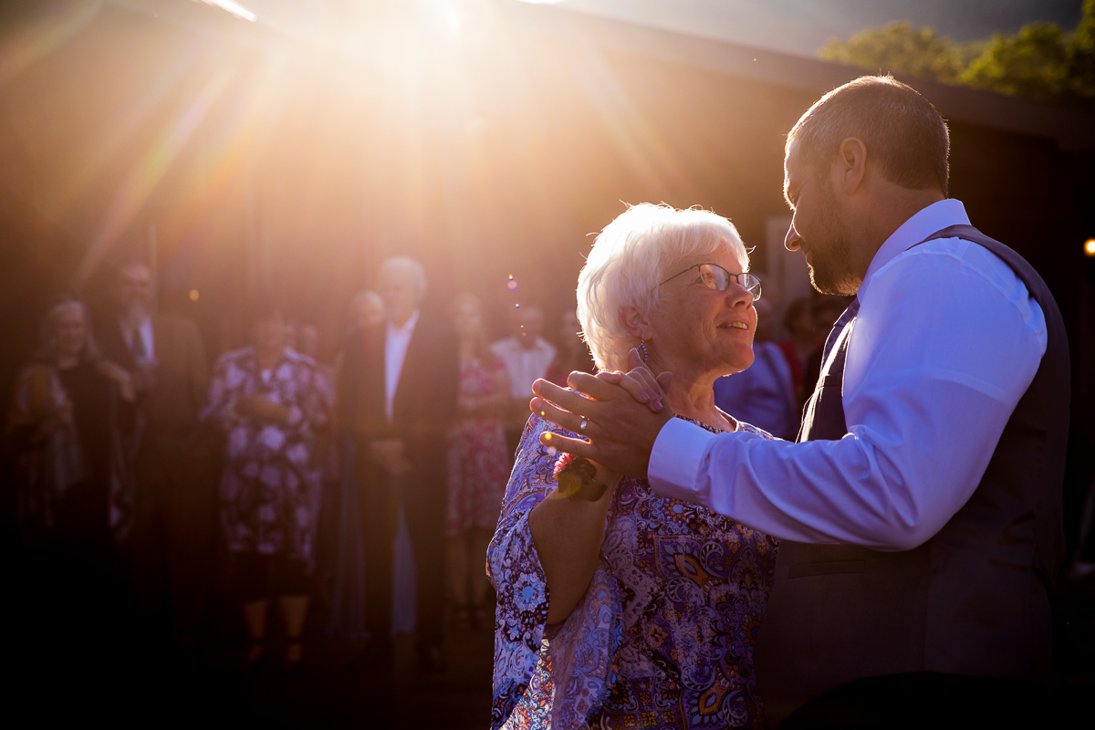 mother son dancing with sunset in background while guests watch
