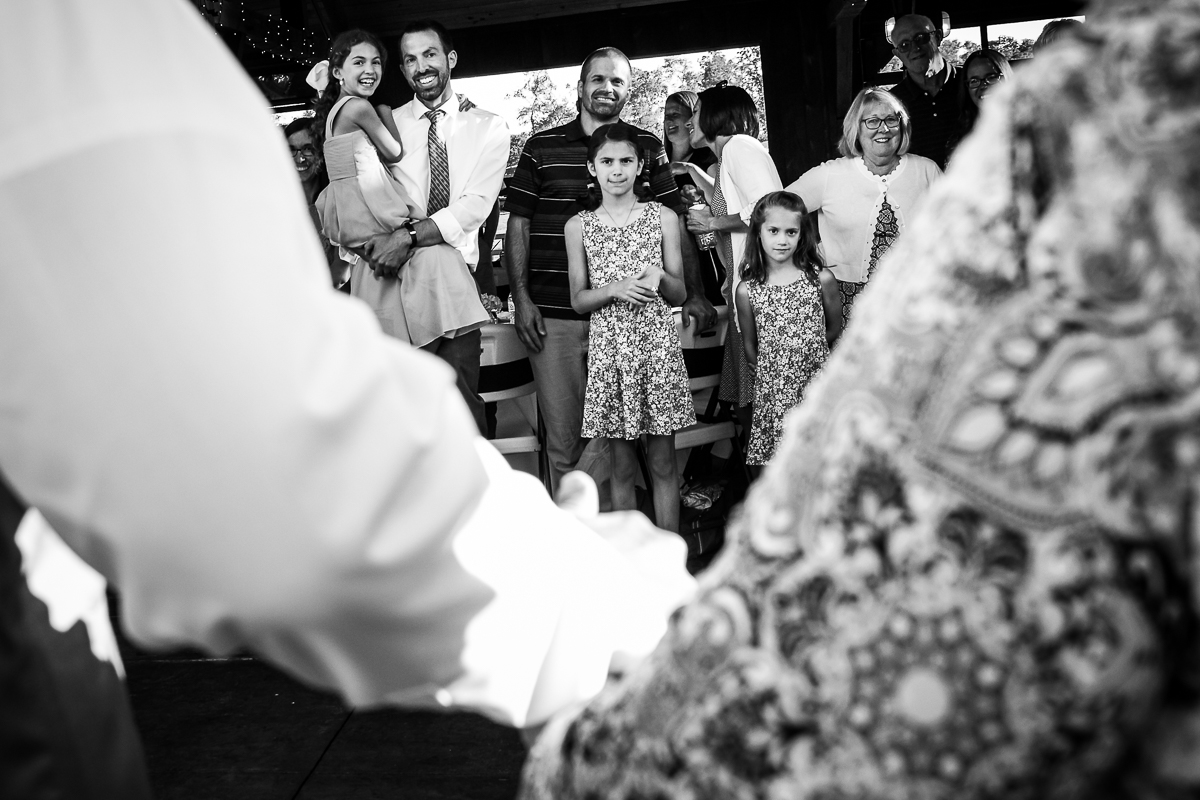 black and white photo of mother son dance with unique perspective of guests watching