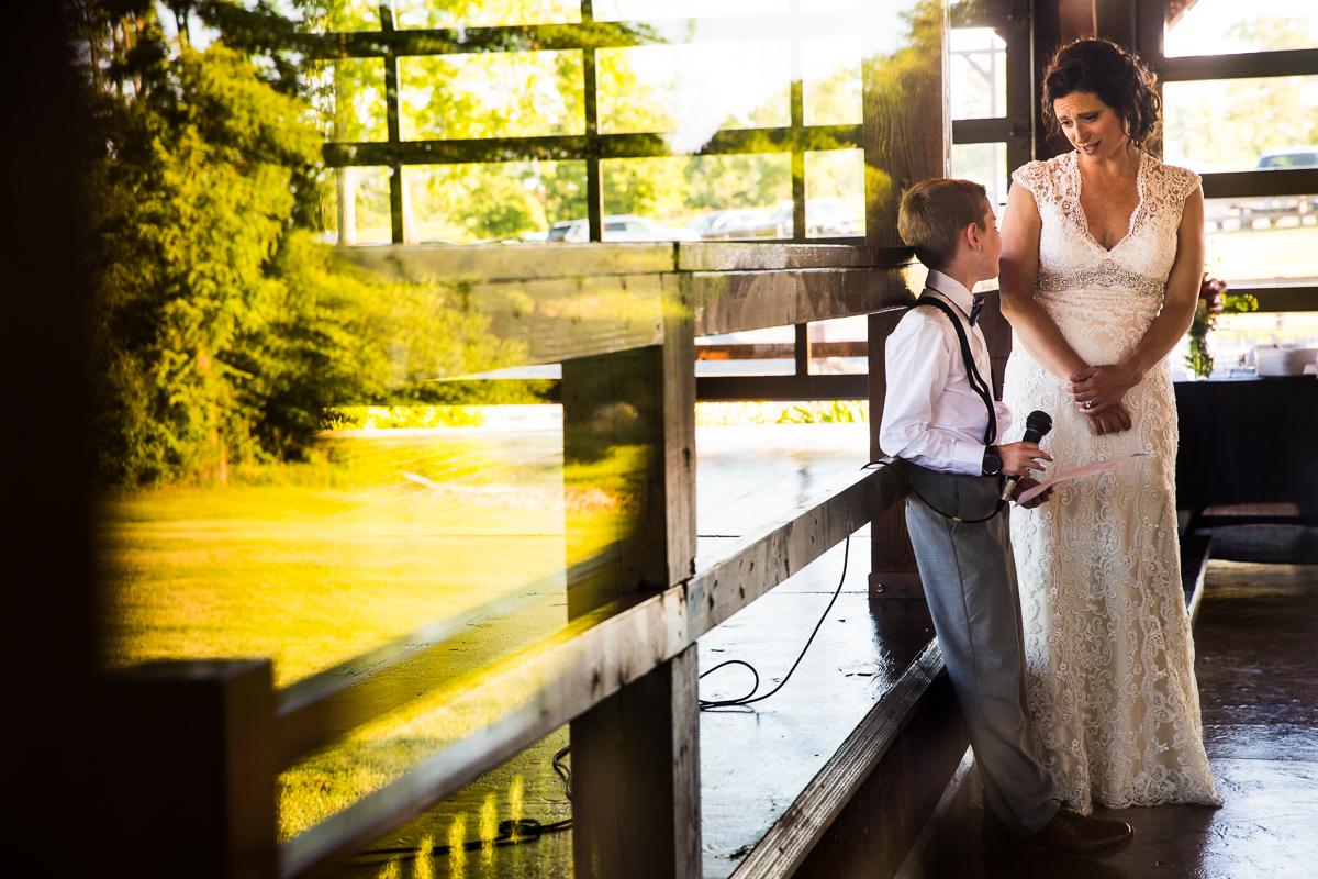 bride smiling at boy giving speech during wedding reception