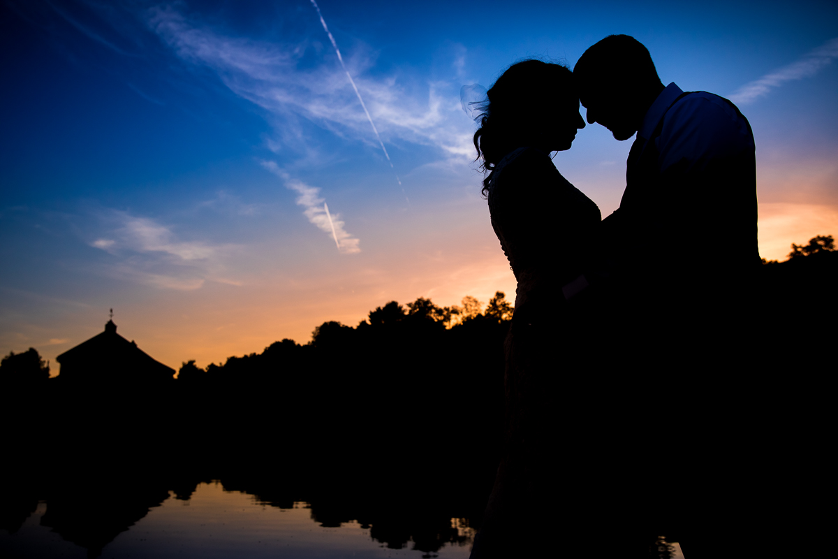 bride and groom silhouetted in front of lake with sunset reflecting best creative award winning artistic micro wedding photographer