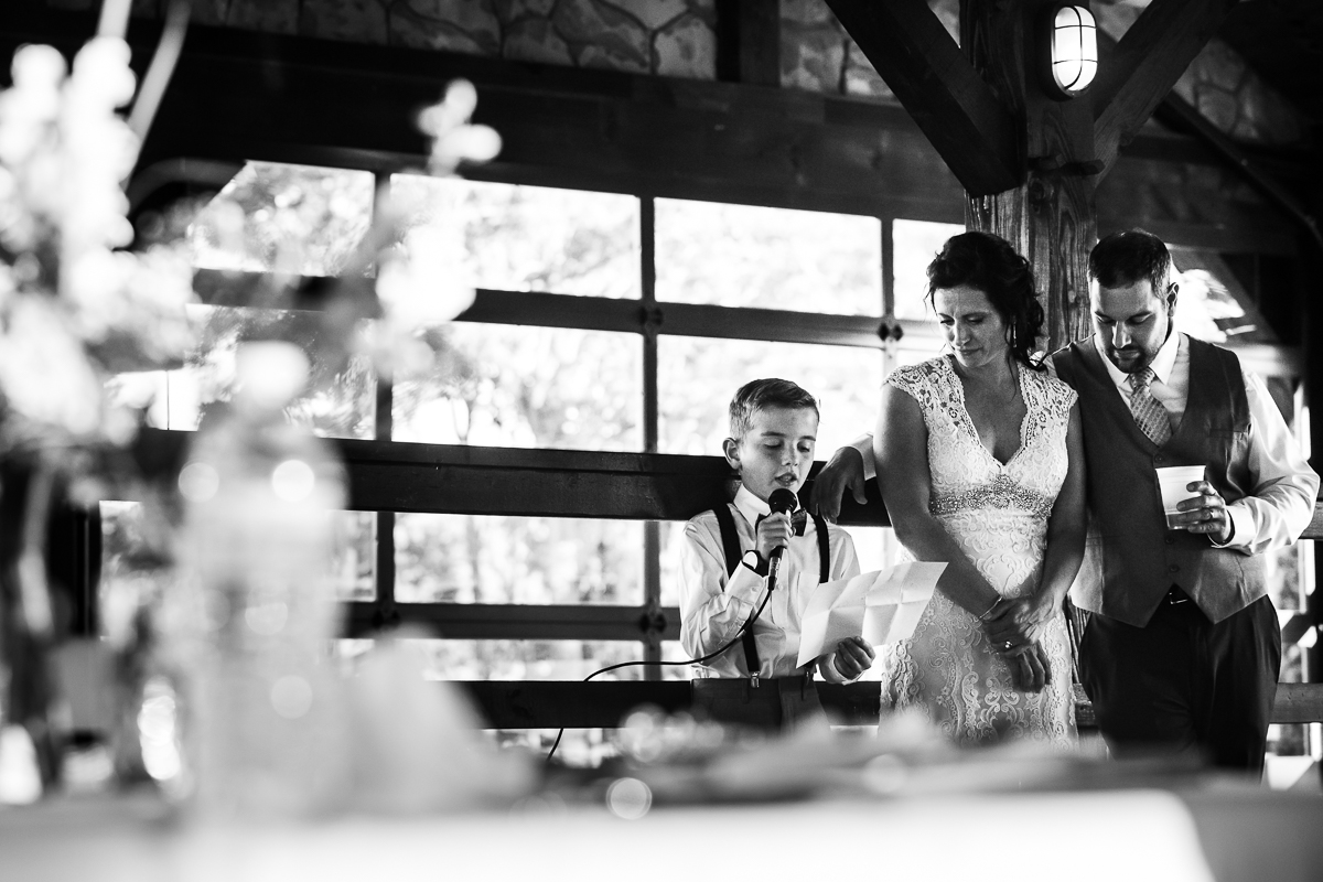 black and white photo of bride and groom standing next to son giving speech during reception at bell mountain estates wedding