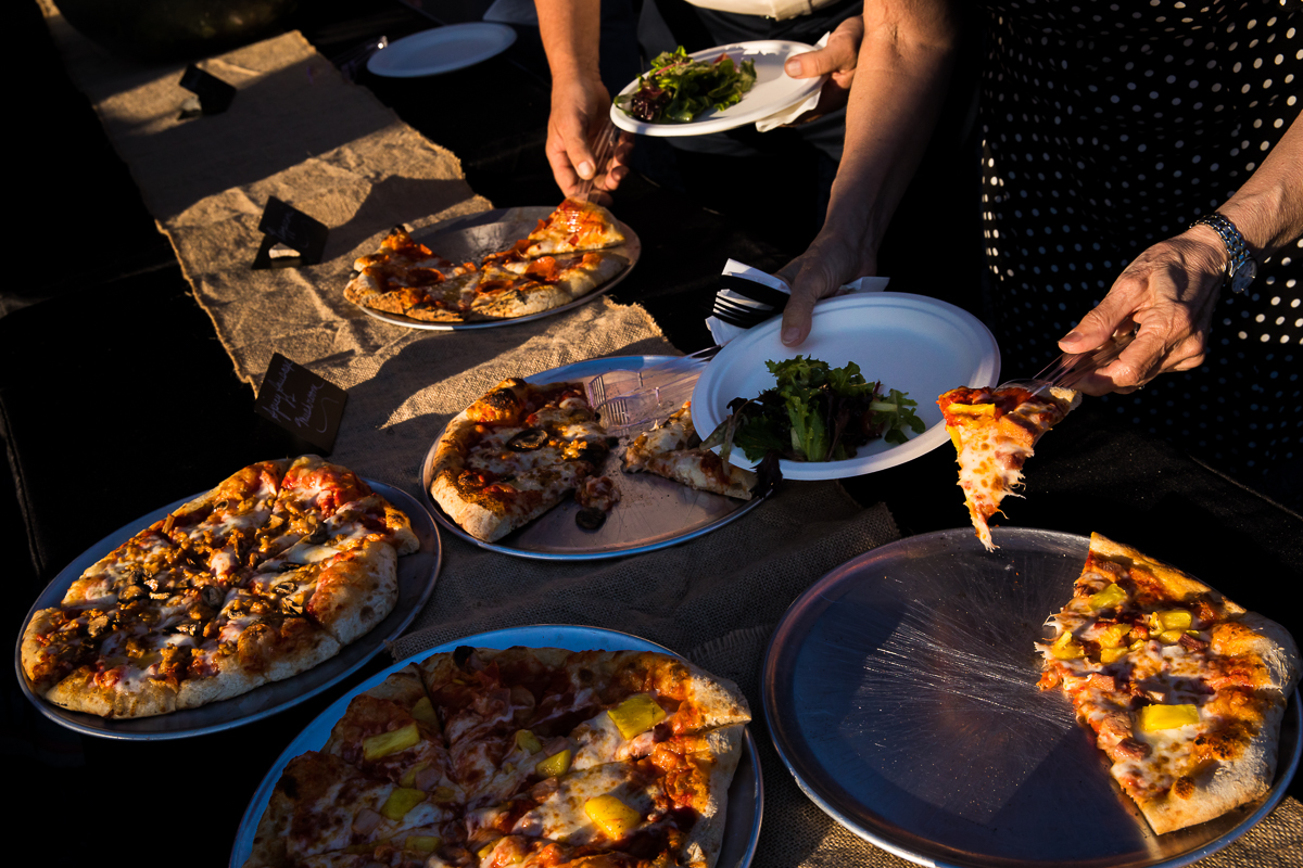 wood fired pizza on trays guests serving during reception