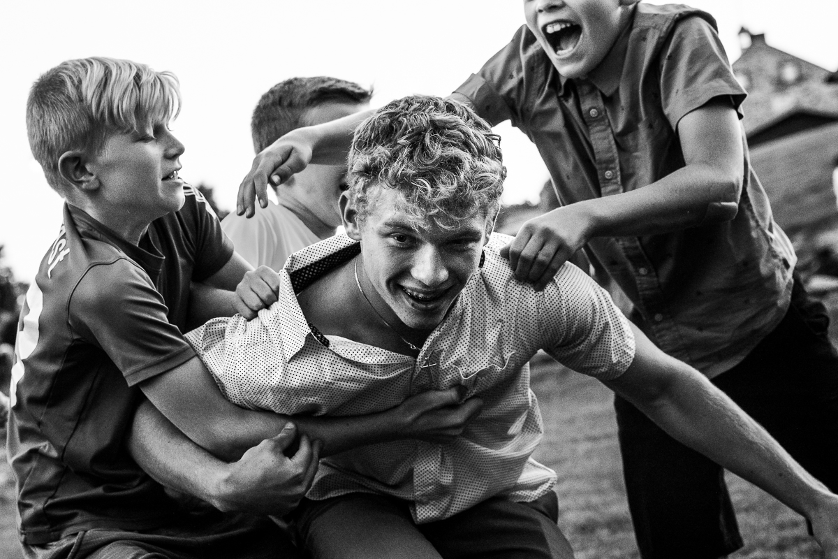 black and white photo of kids playing outside during wedding reception