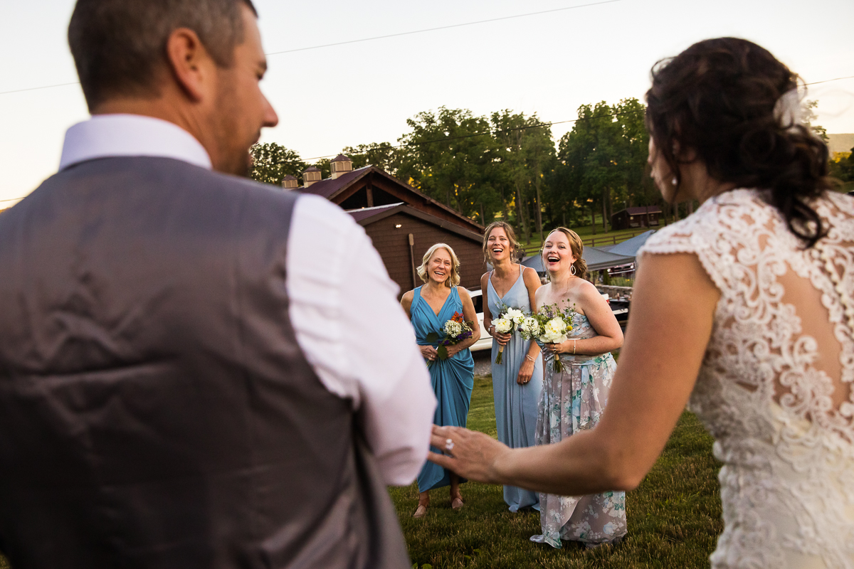 unique perspective of friends looking at bride and groom outside during reception creative artistic wedding photographer