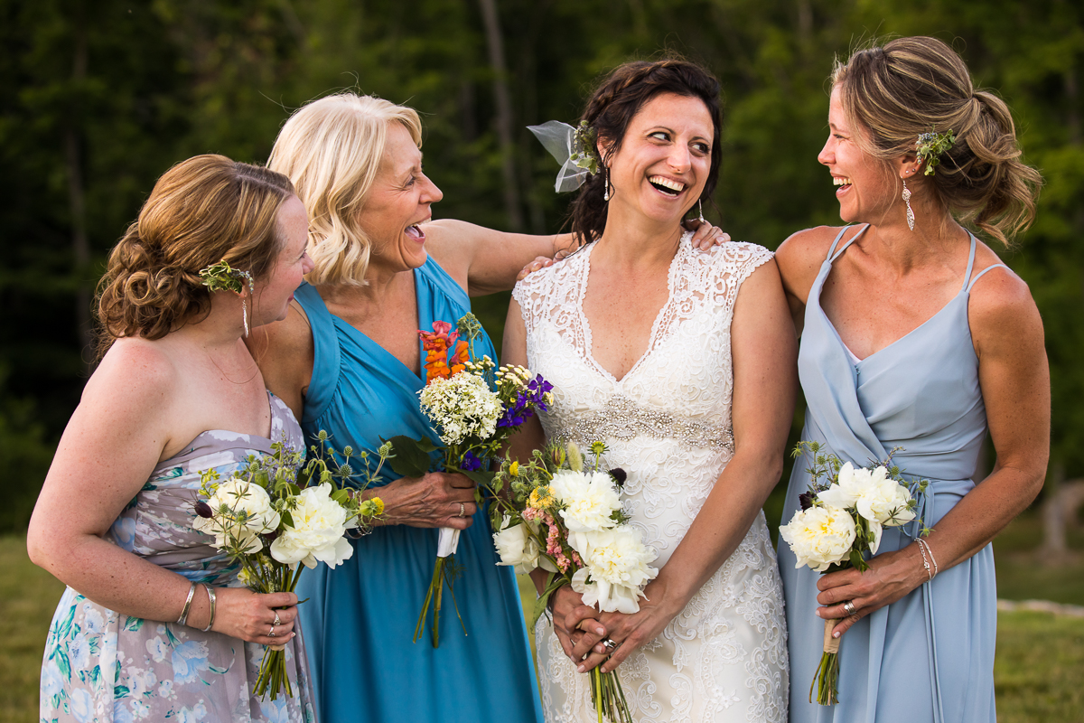 bride smiles as she stands with friends holding bouquet