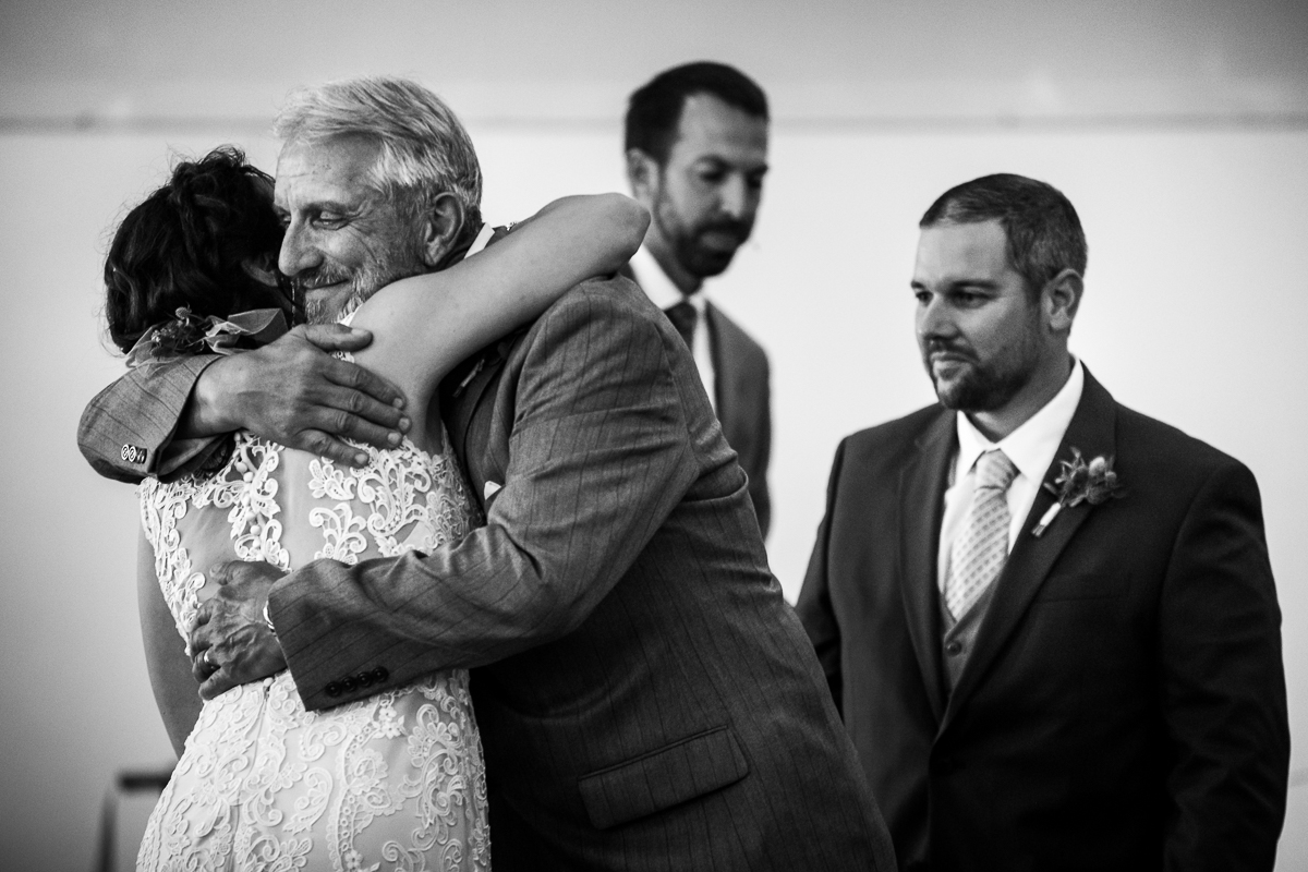 black and white photo of father hugging daughter bride on wedding day while groom looks on touching moment intimate wedding photographer