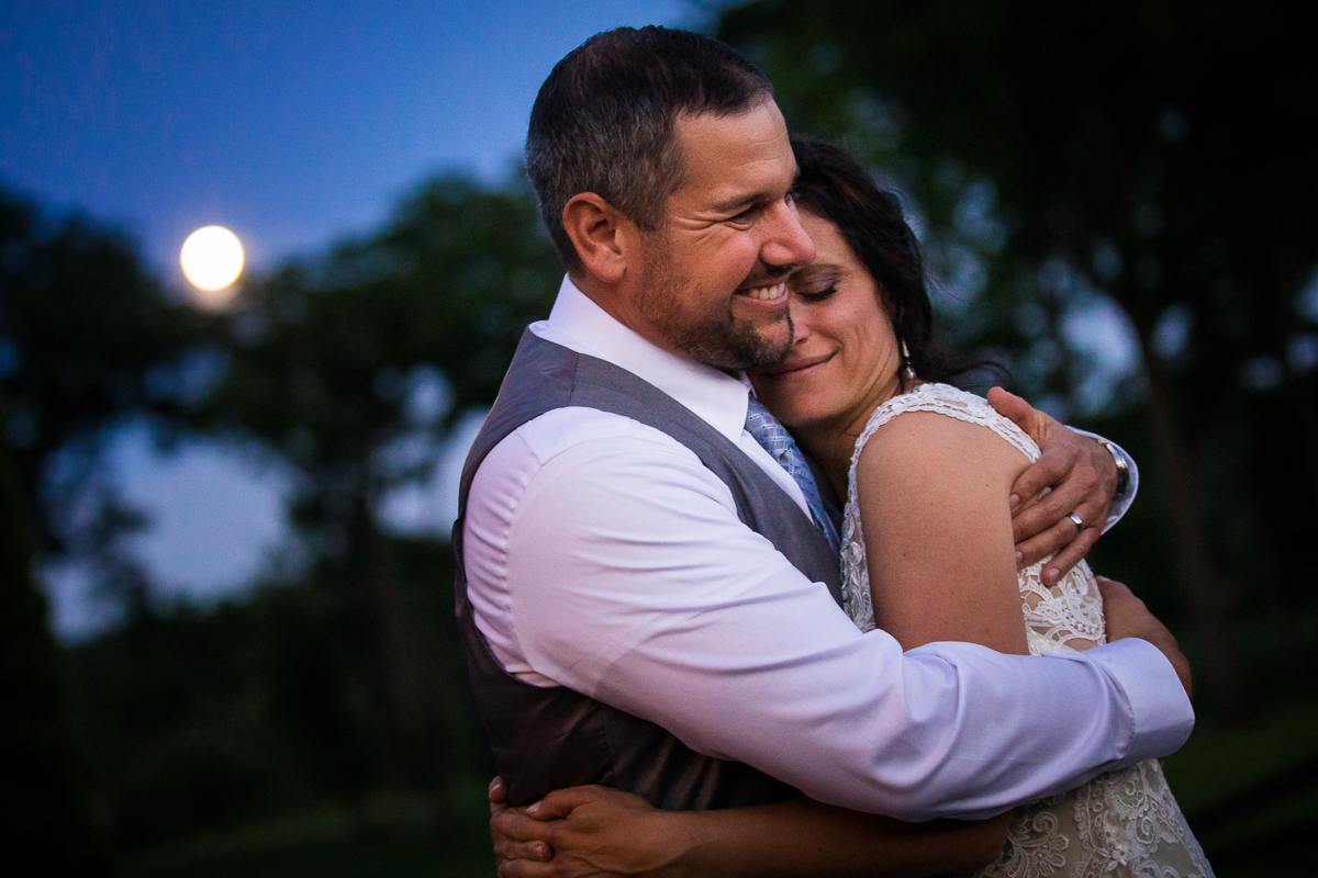 bell mountain estates wedding photographer intimate micro wedding bride and groom hugging outside with sunset in background during twilight blue sky