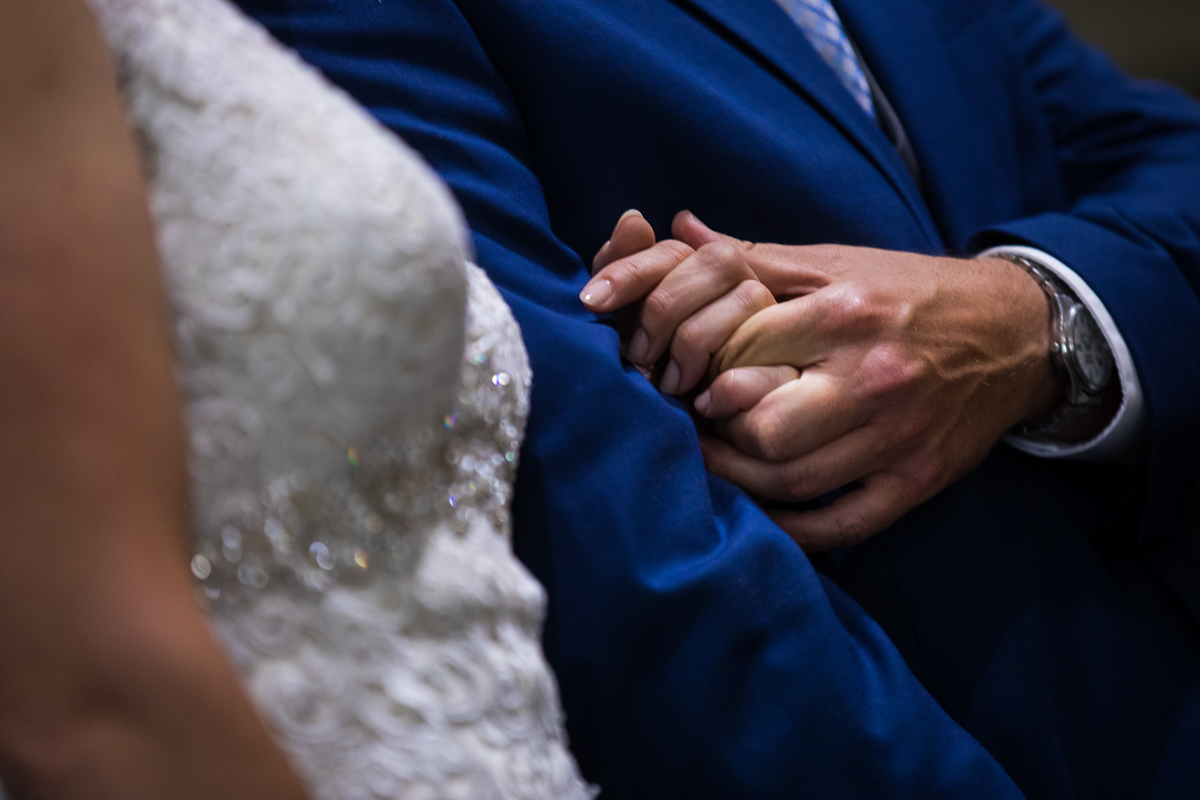 bride and groom close up of hands intertwined during wedding ceremony