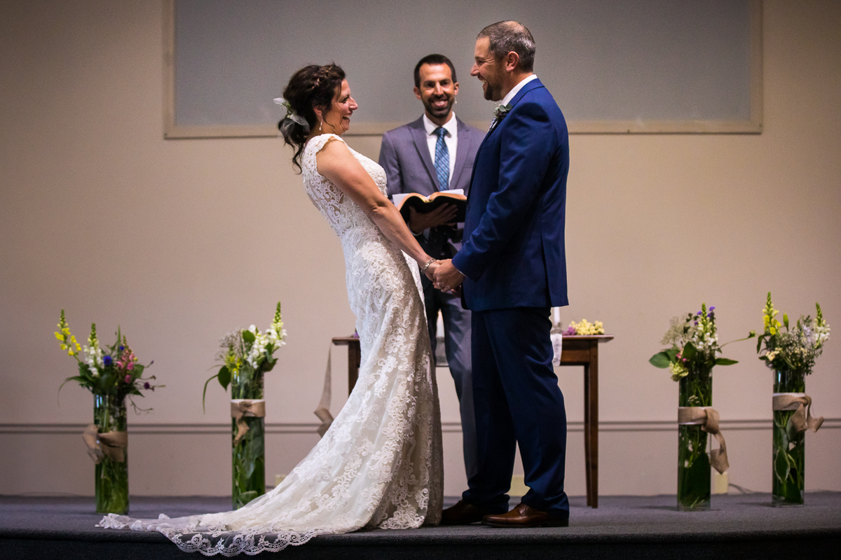 bride and groom holding hands smiling at each other with pastor holding book during ceremony wildflower bouquets in glass vases at altar