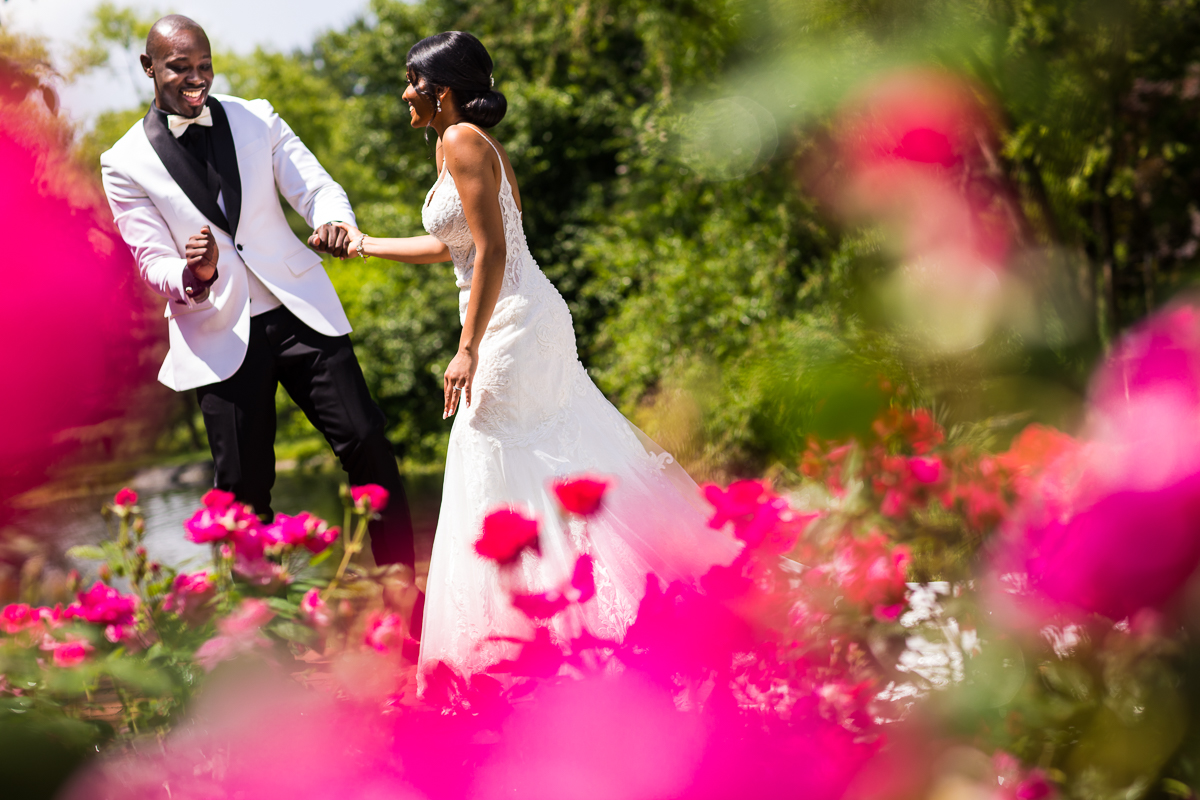 bride and groom in white attire during first look framed by pink roses artistic creative photographer farm at eagles ridge