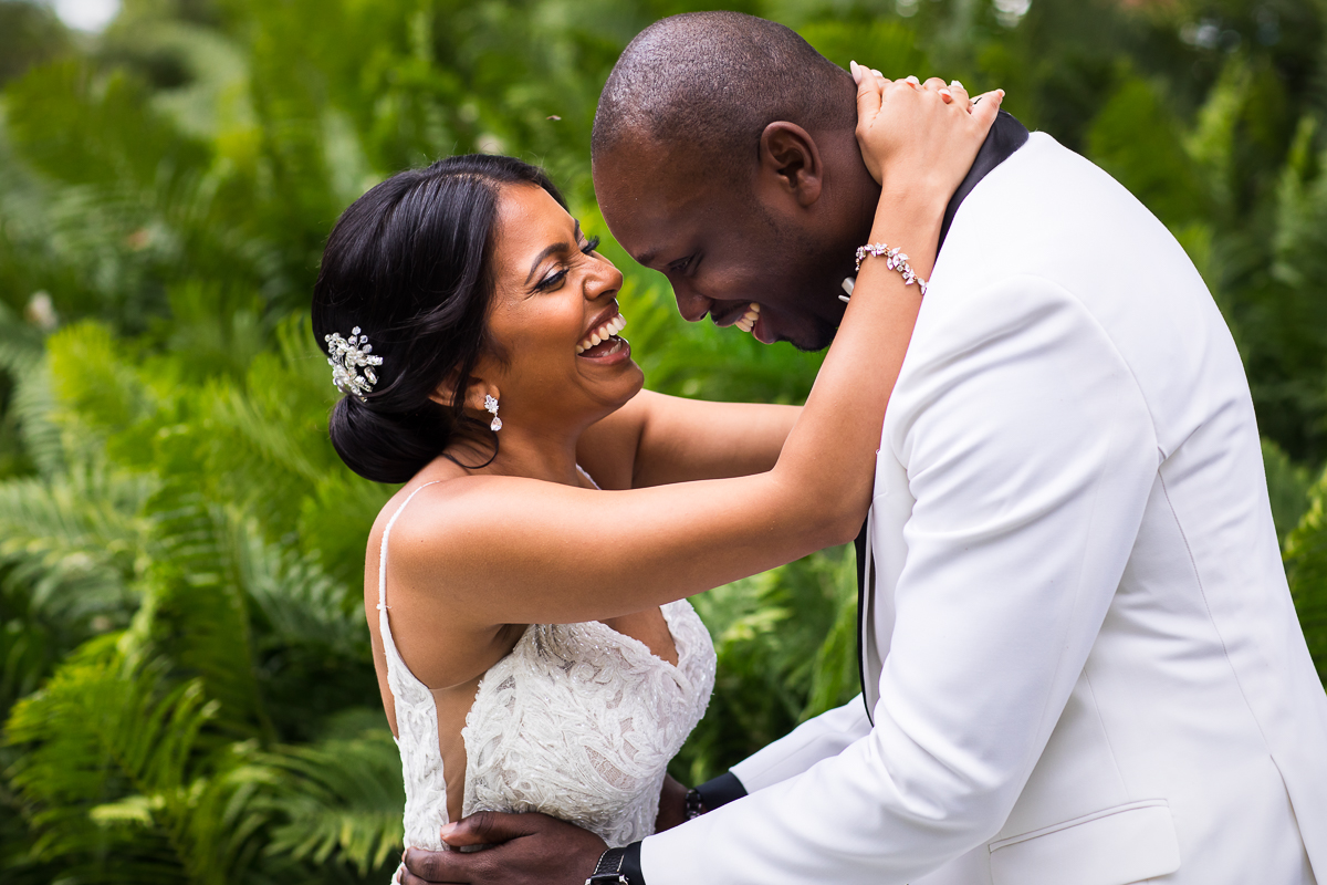 couple hugging and smiling at each other after first look standing in front of palm leaves at farm at eagles ridge creative candid best pa photographer