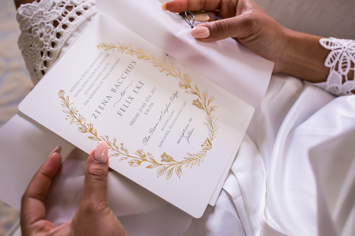 bride holding white and gold wedding invitation while getting ready wearing white lace robe unique wedding photographer