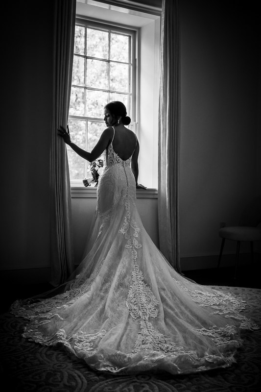 black and white photo of bride standing in front of window in trumpet style lace wedding gown looking back at farm at eagles ridge