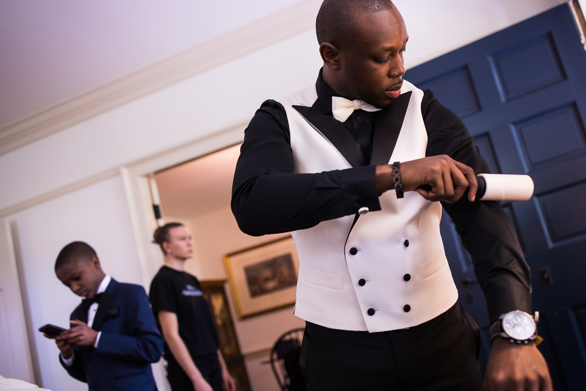 groom using lint roller on black dress shirt under white vest with white bow getting ready photo