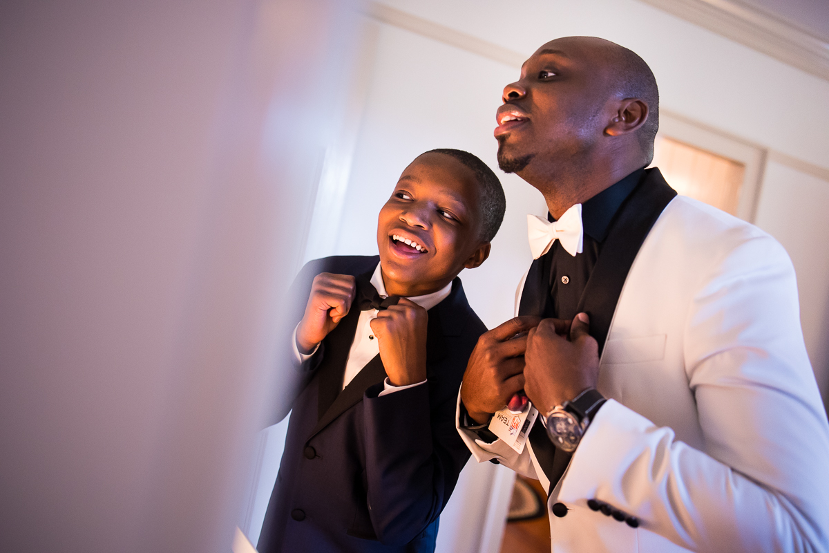 groom and ring bearer fixing bow ties in the mirror before wedding ceremony candid natural authentic Lancaster wedding photographer