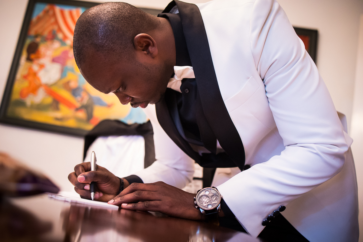 groom signing card on wedding day candid moment photographer award winning