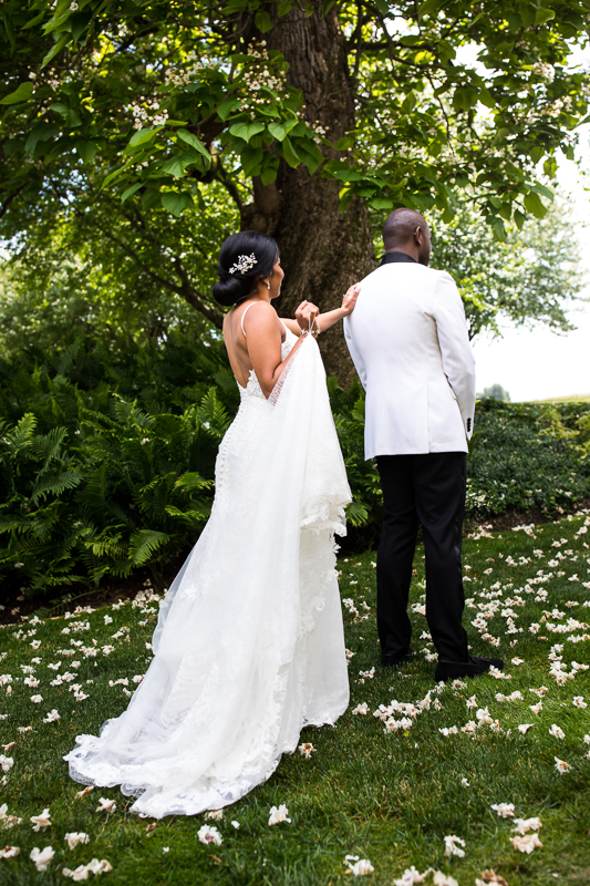 farm at eagles ridge bride tapping groom on shoulder standing outside surrounded by greenery during first look vibrant authentic moments photographer