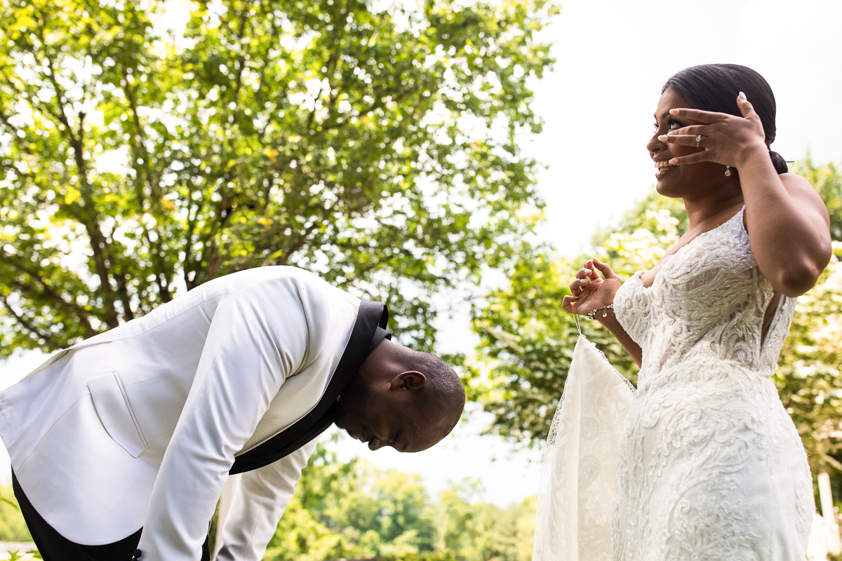 bride wiping tears from eyes after groom cries during first look surrounded by trees
