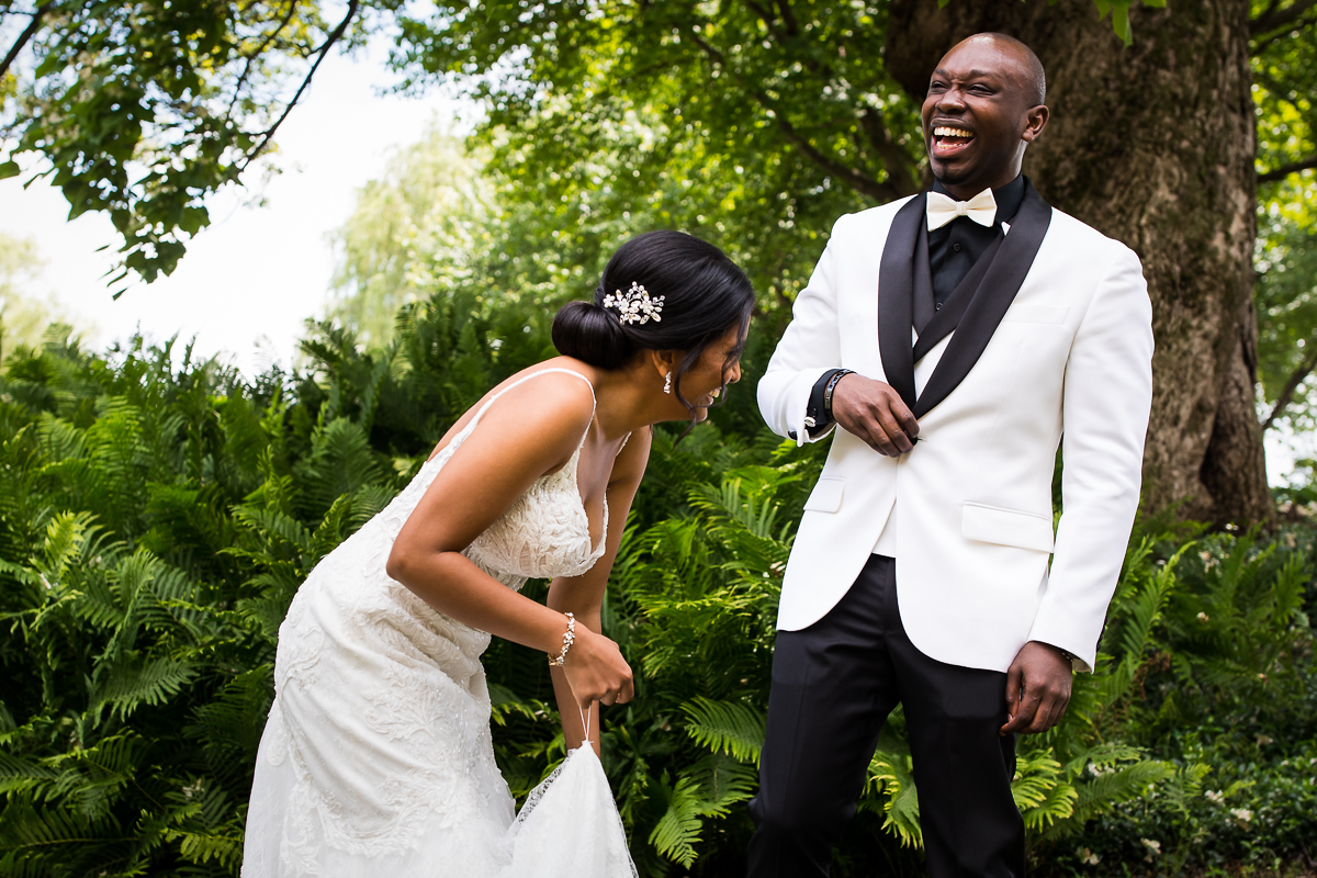best first look reaction bride and groom laughing with each other wearing white on wedding day surrounded by ferns and greenery outside