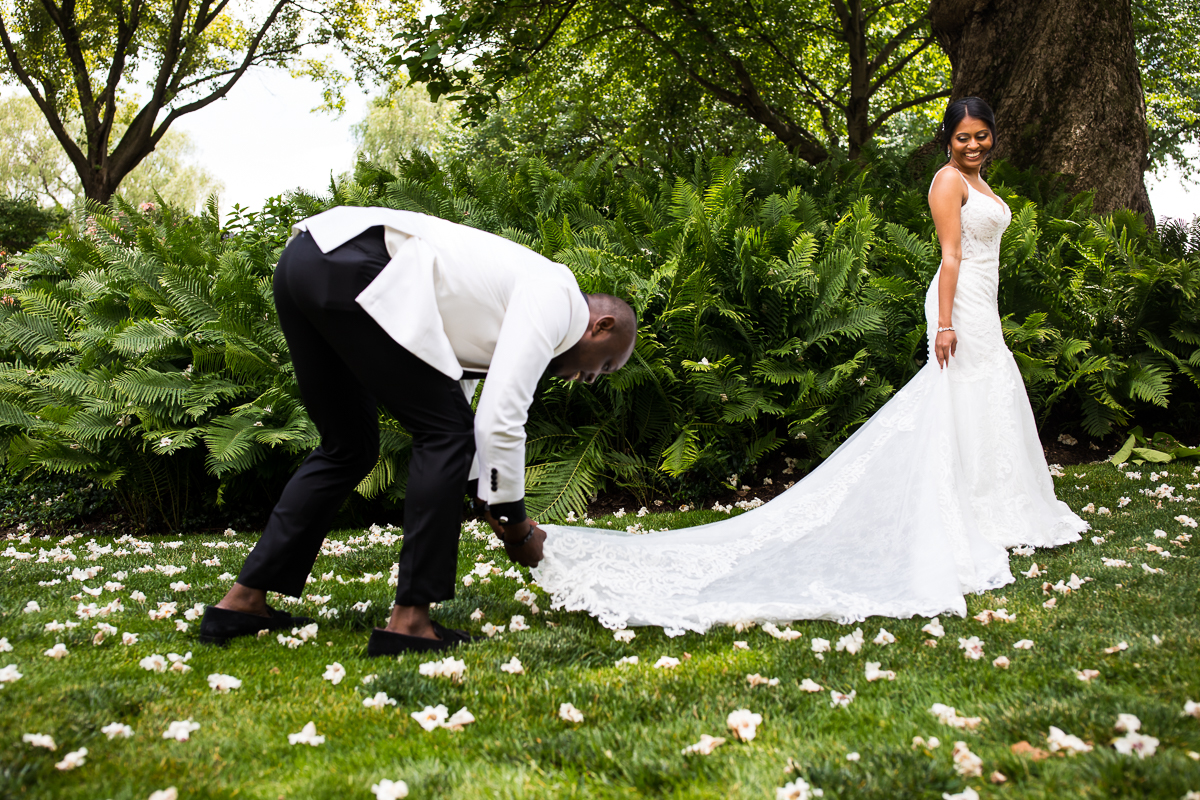 groom fixing bride's wedding dress train outdoors during first look candid award winning photographer central pa