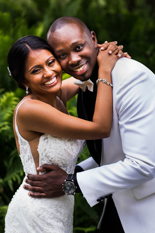 bride and groom hugging each other and smiling looking at camera traditional portrait during first look authentic vibrant wedding photographer Lancaster pa
