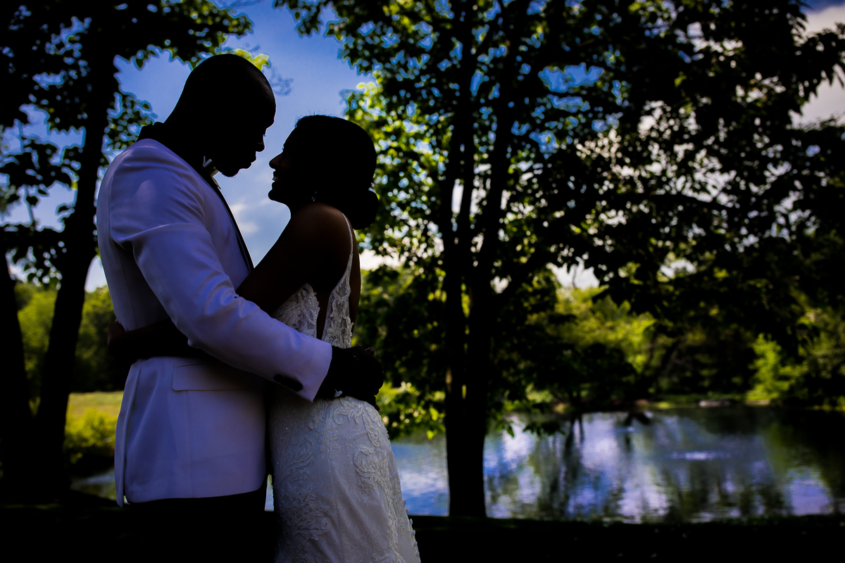 bride and groom holding each other during first look portraits standing in front of pond at farm at eagles ridge bright blue sky in background best award winning photographer
