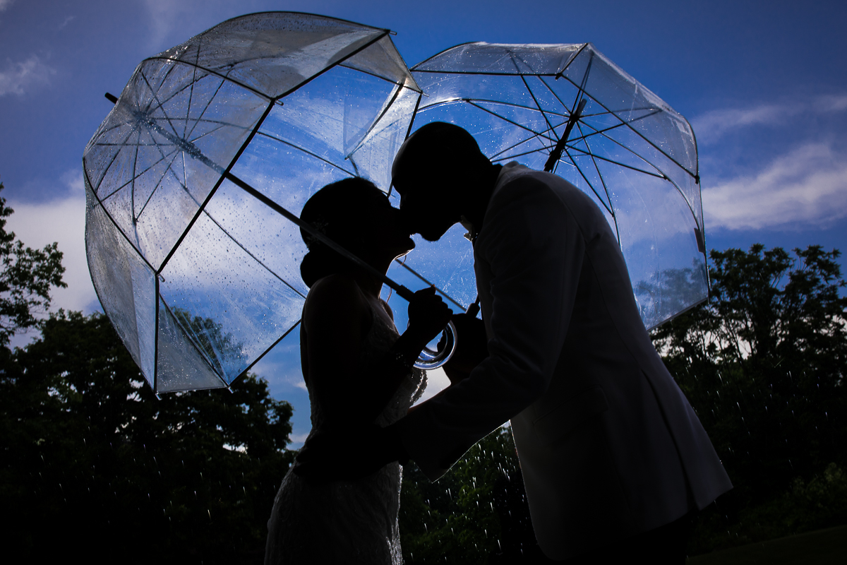 bride and groom kissing while holding clear bubble umbrellas above them silhouetted against vibrant blue sky best creative unique central pa wedding photographer at farm at eagles ridge