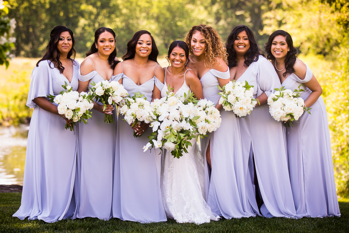 bride standing with bridesmaids wearing light purple bridesmaid dresses holding bouquets of white flowers and greenery colorful vibrant wedding photographer