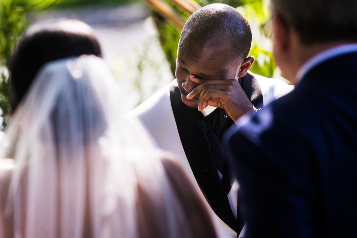 best first look reaction groom crying after seeing bride walk down aisle with dad and bride standing in front of him authentic emotional moment best wedding photographer