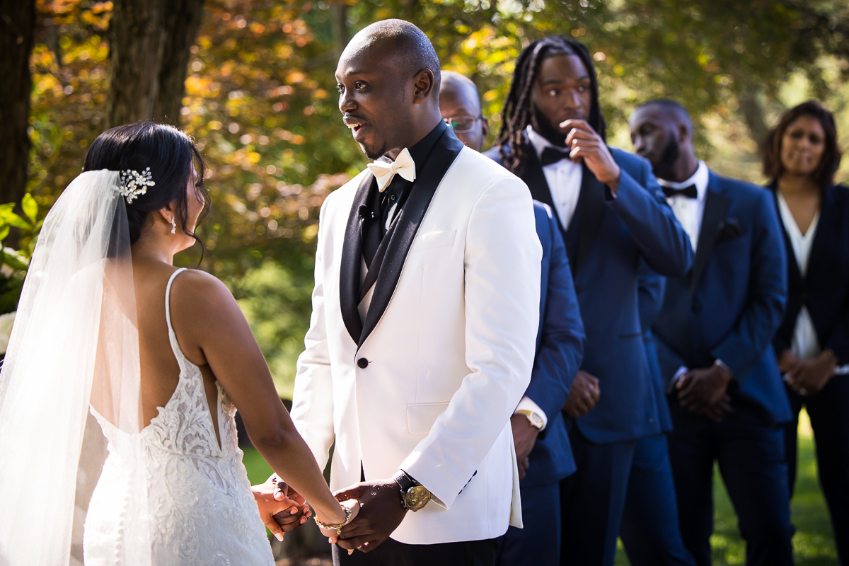bride and groom smiling while holding hands during ceremony groomsmen stand behind