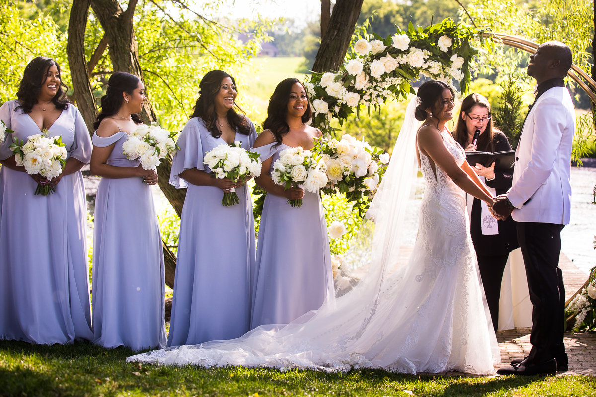 farm at eagles ridge summer wedding bride and groom laugh while holding hands in front of flower arch during ceremony with bridesmaids standing behind them