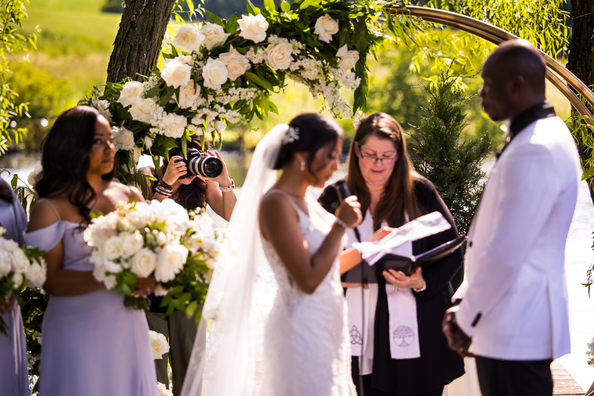 bride reading vows to groom during ceremony while photographer stands behind flower arch to get unique perspective of wedding day
