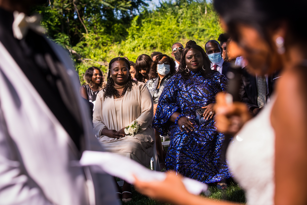 wedding guests smiling while bride reads vows during wedding ceremony