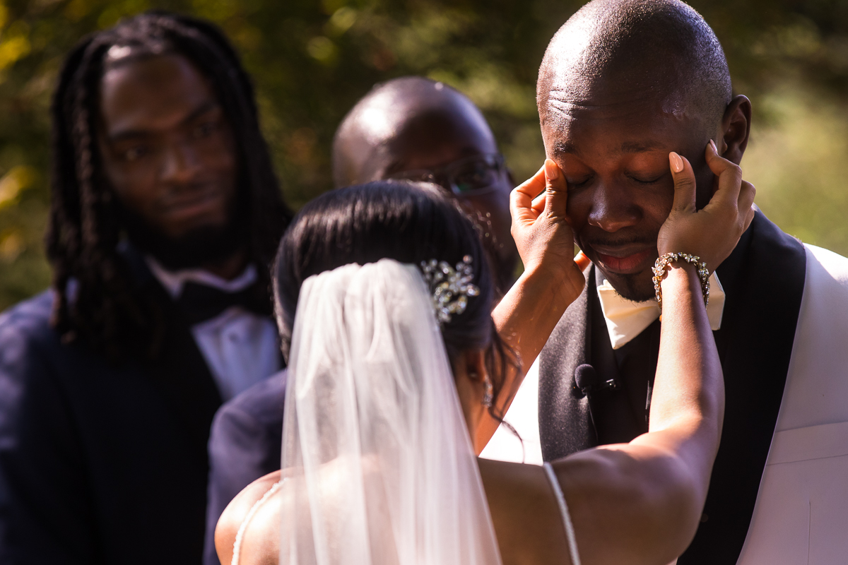 bride wipes away grooms tears during vow reading at wedding ceremony emotional authentic moment captured