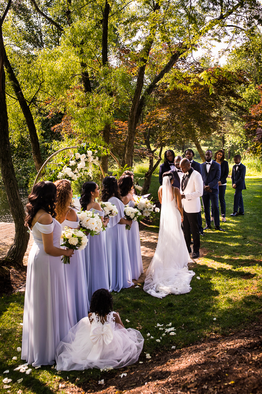 farm at eagles ridge groom reading vows to bride while wedding party looks on during ceremony at farm at eagles ridge wedding photographer
