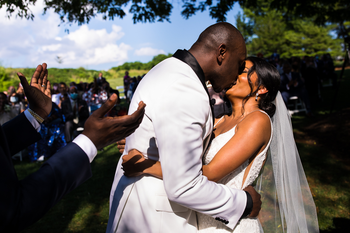 bride and groom share first kiss during wedding ceremony as guests smile and clap to celebrate outside with blue sky and greenery authentic natural emotional best award winning photographer central pa