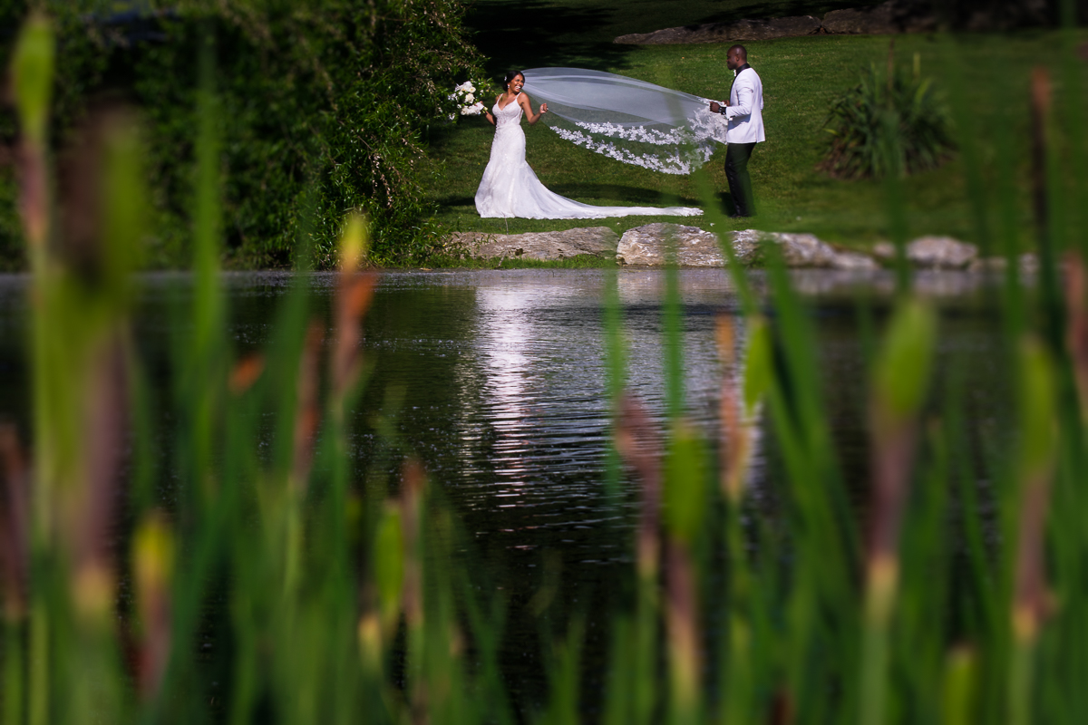 groom fixing bride's veil during portrait time in front of pond at farm at eagles ridge